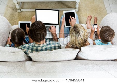 Overhead view of family using various technologies while sitting on sofa at home