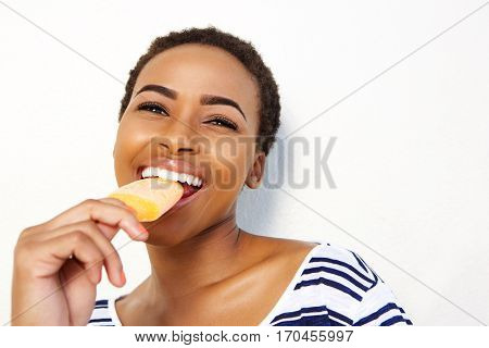 Young Black Female Eating Ice Cream Against White Wall