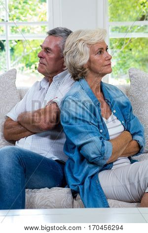 Annoyed senior couple sitting back to back on sofa in sitting room
