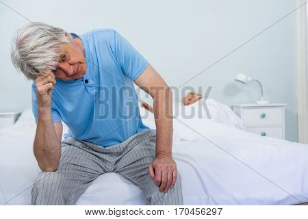 Upset senior man touching head while woman sleeping on bed at home