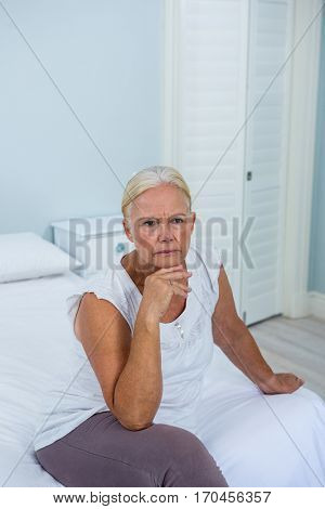 Upset senior woman with hand on chin sitting on bed in bedroom