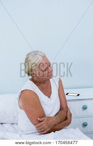 Senior woman having stomach pain while sitting on bed at home