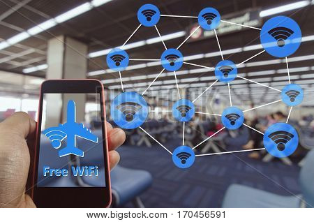 Hand using Smartphone and is using free wifi with wifi icon connection concept  at the airport on blurred background of passengers waiting bording at airport, color tone effect.