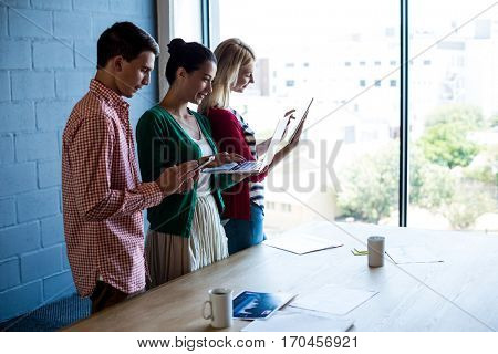 Colleagues using mobile phone, digital tablet and laptop at their desk in the office