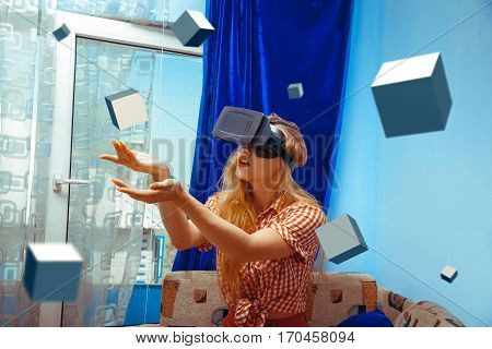 Virtual reality glasses. VR helmet. portrait of serious woman in virtual reality helmet looking away and touching 3d cubes