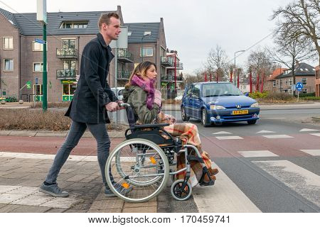 SOEST THE NETHERLANDS - JAN 28: Man pushing a woman in a wheelchair at a zebra crosssing in a Dutch village on Januari 28 in Soest the Netherlands
