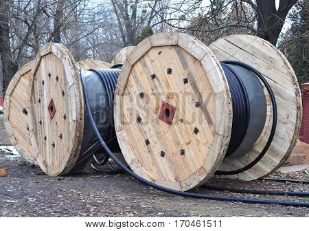 Wooden coil of electric cable and optical fibres on construction site.