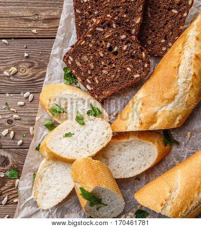 Picture of black and white bread on table with seeds and herbs