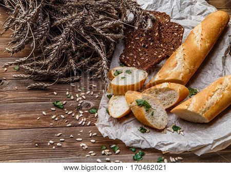 Loaf with grain bread on table with wheat, sunflower seeds