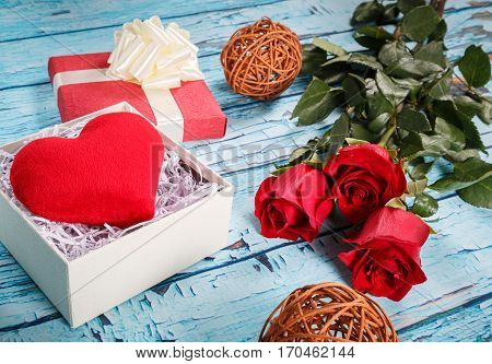 Present consisting from the red heart in the box and bouquet of red roses on the table