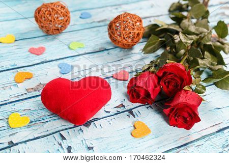Large scarlet heart and bouquet of red roses on a blue wooden table