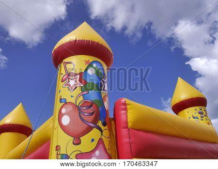 Closeup of children's bouncy castle against blue cloudy sky.