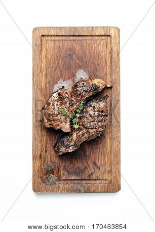 Grilled lamb steak on a cutting board on a white background