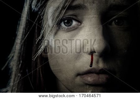 close up portrait of young terrified and sad woman victim of serious domestic violence abuse and attack with blood on her nose crying in sad and scared face expression in male violent aggression