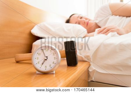 woman sleeping with a hammer to break the alarm clock on the table night