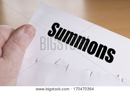 hand holding summons letter, unrecognizable person is summoned to appear in court