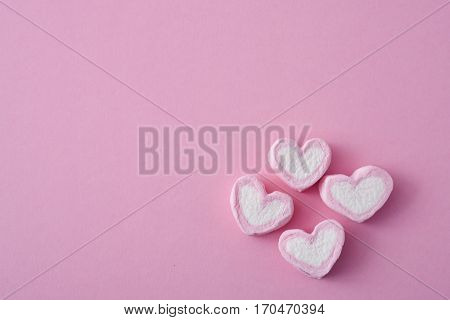 some pink and white heart-shaped marshmallows on a pink background, with a negative space on the left