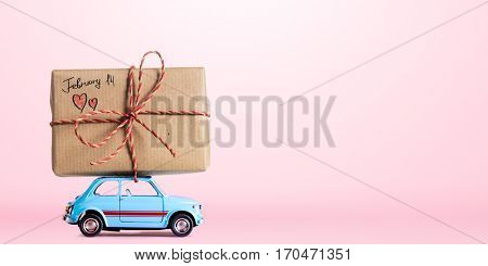 Blue retro toy car delivering gift box with February 14 caption for Valentine's day on pink background