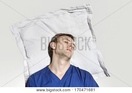 Young man reclined her head on pillow over colored background