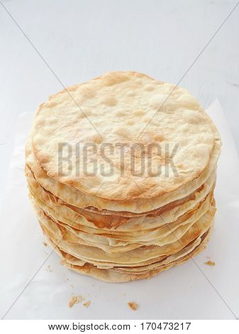 Cooking process. Preparing multi-layered cake. Crusts for homemade mille feuille. Big pile of fresh pancakes. Top view.