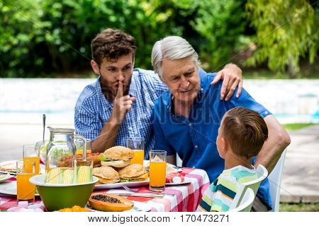 Man gesturing silence while son talking with grandfather at dinning table in lawn