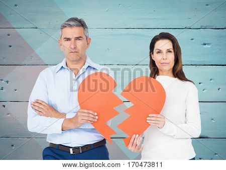 Portrait of depressed couple holding broken heart against wooden background