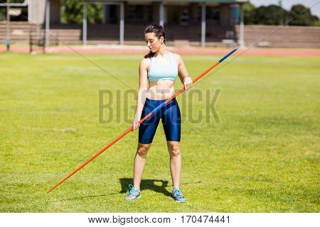 Female athlete holding a javelin in stadium on a sunny day