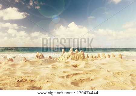Dreamy Sand castle built on seashore, ocean background. Soft retro warm toned, pastel colors, lens flare effect.