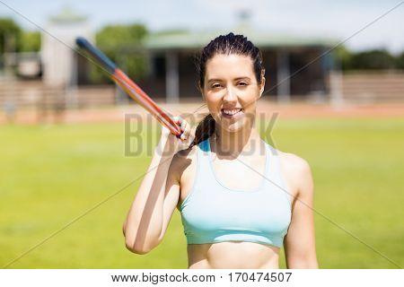 Portrait of happy female athlete holding a javelin in stadium