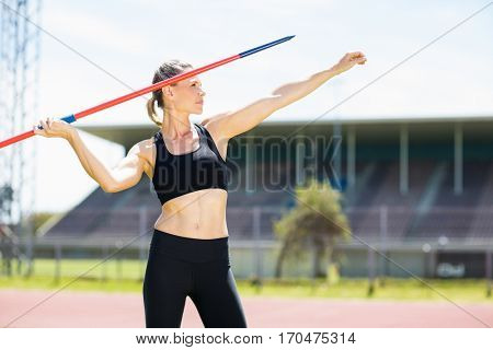 Confident female athlete about to throw a javelin in the stadium