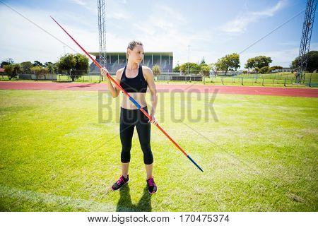 Female athlete holding a javelin standing in stadium