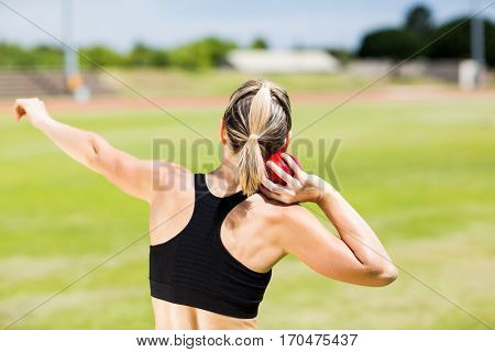 Rear view of female athlete preparing to throw shot put ball in stadium