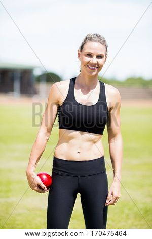 Portrait of happy female athlete holding a shot put ball in stadium