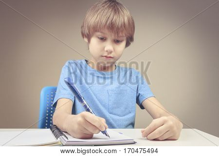 Boy using pen and writing on spiral paper notebook. Boy doing his homework exercises. School, education concept