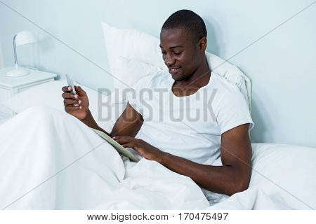 Happy young man using digital tablet and phone on bed in bedroom