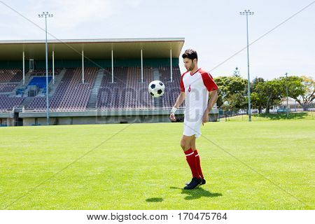 Athlete juggling the football with his feet in stadium