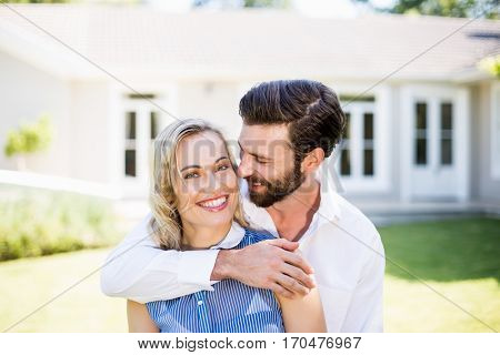 Romantic couple embracing each other outside the house