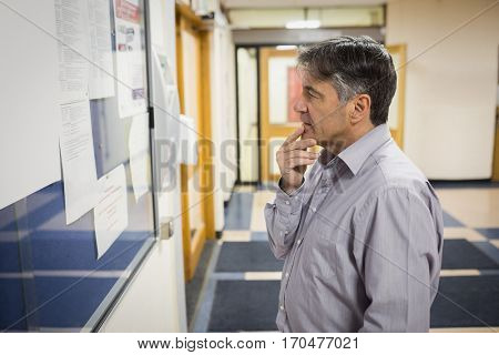 Professor reading notice board in college
