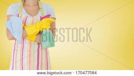 Mid section of female cleaner standing with napkin and spray bottle against yellow background