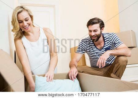 Young couple unpacking carton in new house