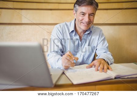 Portrait of happy professor writing in book at desk in classroom
