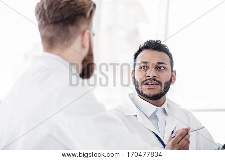 Willing bearded asian physician speaking with colleague in hospital room at conference