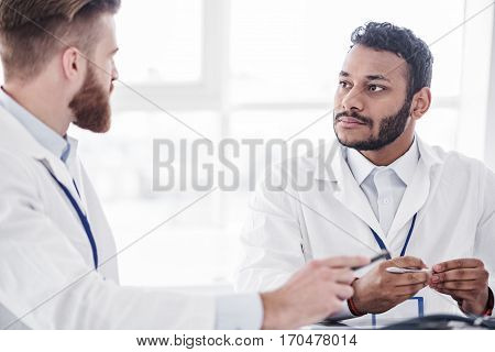 Serene bearded asian doctor hearing affiliate in apartment of clinic during meeting