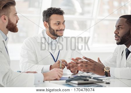 Outgoing therapeutic arguing with colleagues while sitting near them at conference in hospital