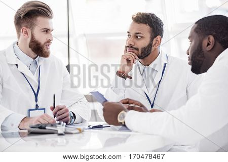 Calm young therapeutic listening his affiliates while sitting at desk during meeting in office of clinic