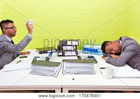Indian businessman throwing paper at his sleeping twin