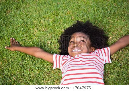 Smiling boy lying down in grass in a park