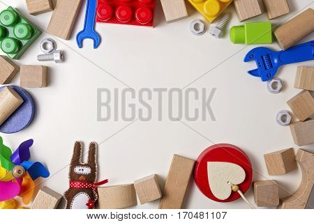Kids toys on white background as bord frame with copy space for text. Top view