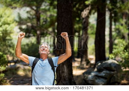 Hiker smiling and throwing arms on the wood