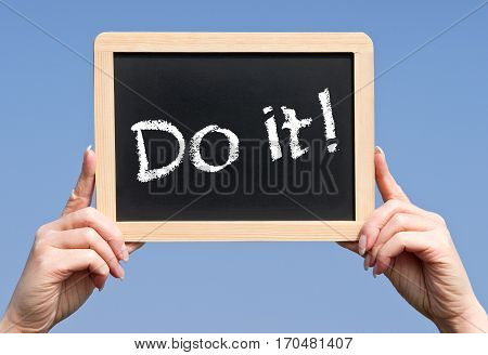 Do it - female hands holding chalkboard with text